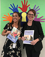 meg lopez and colleague holding wida booklets