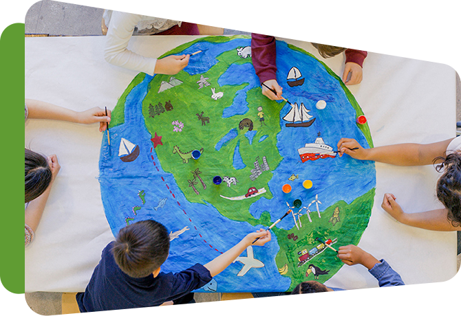 children in a circle reaching across a large drawing of a globe