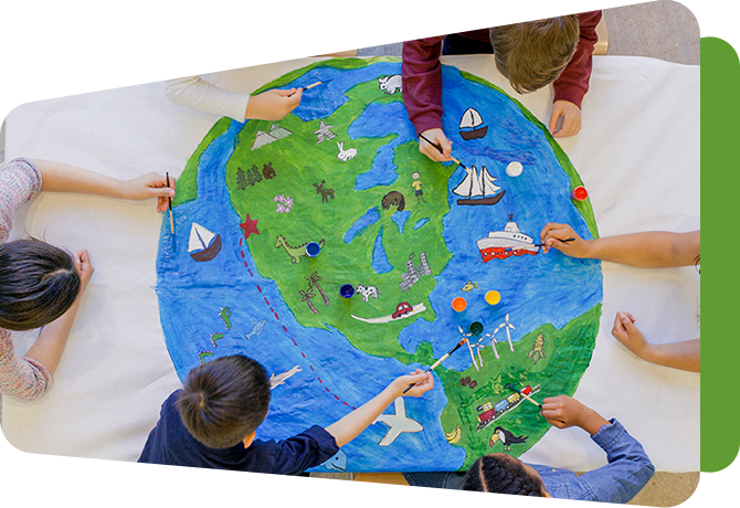 circle of children reaching across a large drawing of a globe
