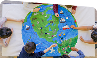 circle of children reaching in to a large drawing of a globe