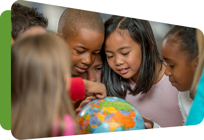 group of small children around a globe