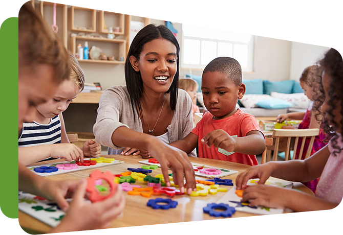 early care practitioner with children at table, arranging blocks