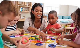 early care practitioner with three young children at a table arranging blocks