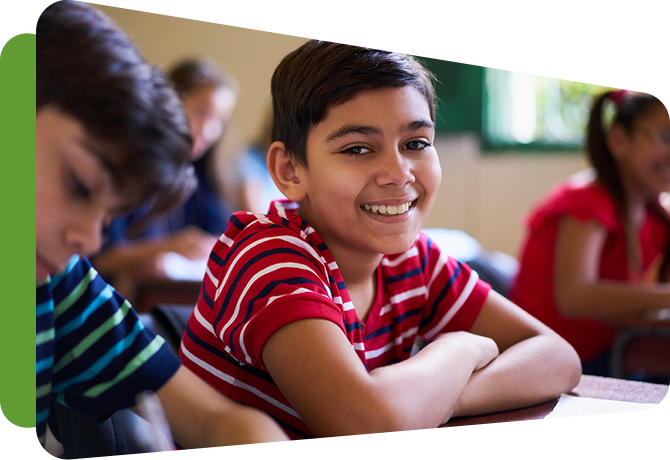 smiling boy at desk in classroom with other students