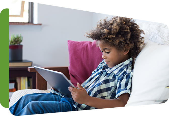boy sitting in chair reading from tablet