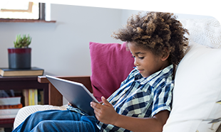 boy reading from tablet on couch
