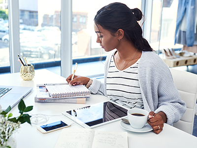 woman at desk working on tablet