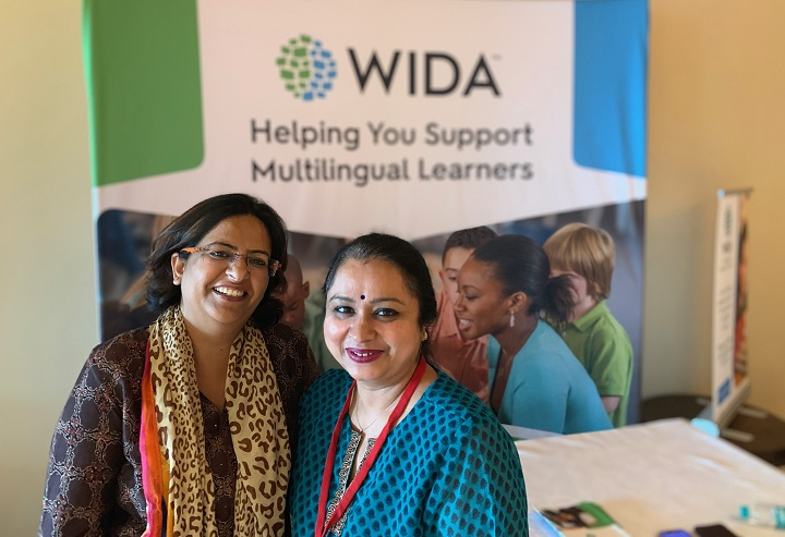 Women standing in front of banner that says WIDA helping you support multilingual learners