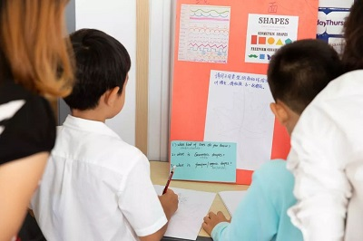 a teacher and three students looking at an informational poster